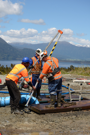 The safety officer sets up a rescue tripod at the top of an abandoned oil well on the West Coast before sending workers into a  confined space.