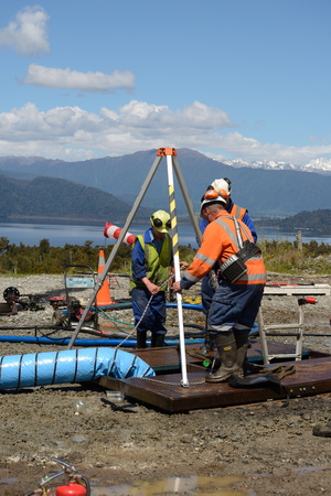 MOANA, NEW ZEALAND, OCTOBER 27, 2017: The safety officer sets up a rescue tripod at the top of an abandoned oil well before sending workers into a  confined space. 에디토리얼
