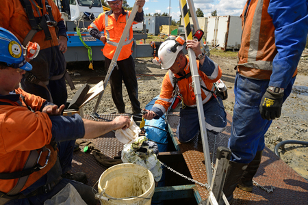 MOANA, NEW ZEALAND, OCTOBER 27, 2017: The safety officer checks methane levels at the top of an abandoned oil well before sending workers into a  confined space.