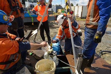 MOANA, NOUVELLE-ZÉLANDE, LE 27 OCTOBRE 2017: L'agent de sécurité vérifie les niveaux de méthane au sommet d'un puits de pétrole abandonné avant d'envoyer les travailleurs dans un espace confiné. Banque d'images - 92635456