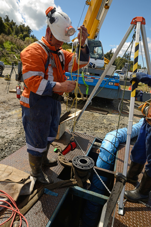 The safety officer checks methane levels at the top of an abandoned oil well on the West Cost before sending workers into a confined space.