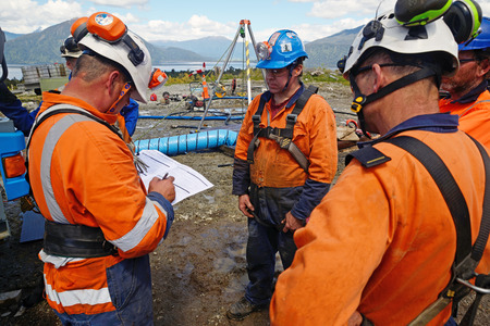MOANA, NEW ZEALAND, OCTOBER 27, 2017: The safety officer conducts a safety meeting at an abandoned oil well (behind the group) before permitting workers into a confined space. 報道画像