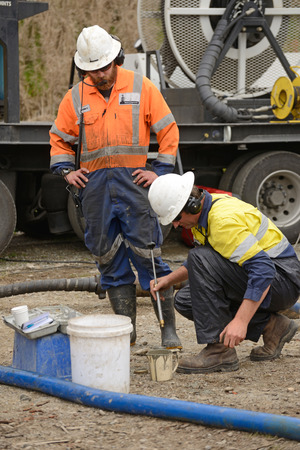 MOANA, NEW ZEALAND, OCTOBER 27, 2017: Well engineers weigh a sample of concrete as they pump concrete into an abandoned well. Editorial