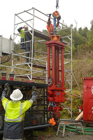 MOANA, NEW ZEALAND, OCTOBER 27, 2017: Engineers discuss how to set up a huge hydraulic jack on top of an old oil well to remove the steel casing.