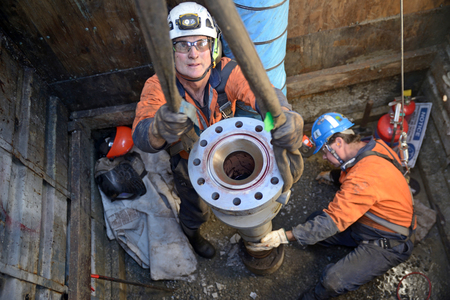 MOANA, NEW ZEALAND, OCTOBER 27, 2017: Engineers place a new flange on top of an oil well in preparation for capping the well. They are working in a ventilated confined space. Editorial