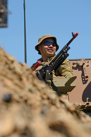 GREYMOUTH, NEW ZEALAND, NOVEMBER 18, 2017: An unidentified soldier stands by his Mag 58 GM machine gun at an open day run by the New Zealand armed forces. Editorial