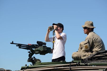 GREYMOUTH, NEW ZEALAND, NOVEMBER 18, 2017: An unidentified schoolboy scans the horizon with binoculars at an open day run by the New Zealand armed forces. The machine gun is a Mag 58 GM. Editorial