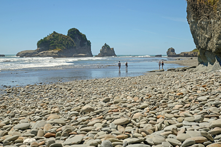 tourists enjoy the scenery at low tide on a West Coast beach, South Island, New Zealand Stock Photo