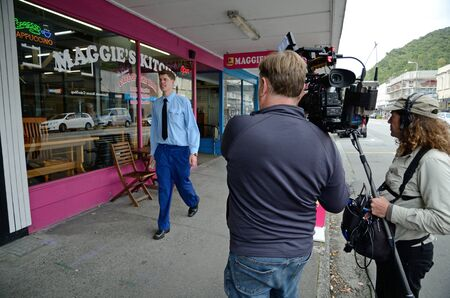 GREYMOUTH, NEW ZEALAND, MARCH 23, 2018: A film crew record the progress of a man in the main street of Greymouth.
