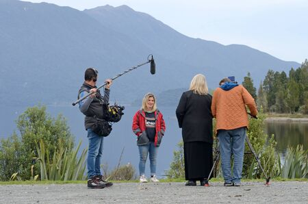 MOANA, NEW ZEALAND, APRIL 23, 2018: A film crew interviews a young woman at the edge of Lake Brunner for a documentary story.
