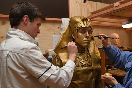 Make-up artists prepare an actor for his role as an egyptian statue in a stage production