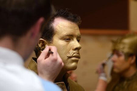 A make-up artist applies gold paint to an actors face before a performance