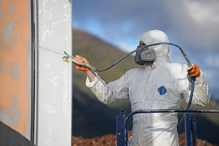 Tradesman spray paints the steel beams on a construction site