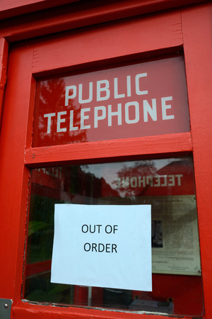 an out of order sign on a public telephone box