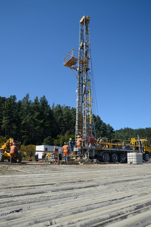 DOBSON, NEW ZEALAND, OCTOBER 13, 2018: Engineers feed the drill string down an old gas well in preparation for capping the well. Editorial