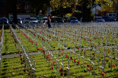 CHRISTCHURCH, NEW ZEALAND, APRIL 20, 2018: A family visits a field of crosses representing those who died in the Great War. The memorial was set up for Anzac Day in Christchurch, New Zealand