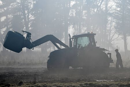 A farmer checks his front end loader in the fog while feeding out on a West Coast dairy farm, New Zealand