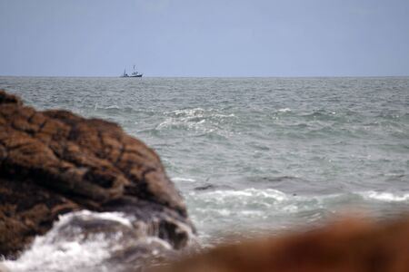 A small fishing vessel sails past Charleston on the West Coast