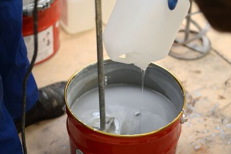 Detail of a tradesman mixing a batch of epoxy flooring compound with an electric powered stirrer