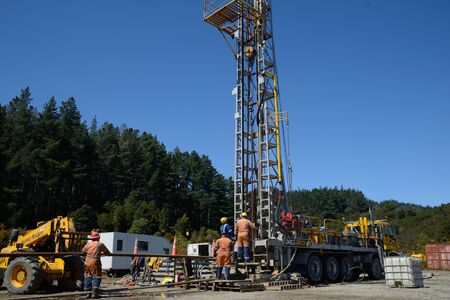 DOBSON, NEW ZEALAND, OCTOBER 13, 2018: Engineers feed the drill string down an old gas well in preparation for capping the well.