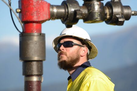 MOANA, NEW ZEALAND, OCTOBER 27, 2017: An unidentified engineer checks the guage during a pressure test on an abandoned oil well in preparation for capping the well. Éditoriale