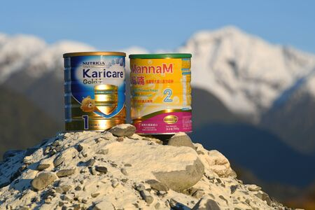 WEST COAST, NEW ZEALAND, JULY 25, 2019: Two tins of Infant milk powder sits on a mountain of milk powder with the snowy Southern Alps in the background