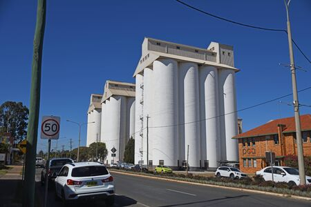 KINGAROY, AUSTRALIA, JULY 30 2019: Power poles frame the iconic Kingaroy Peanut Silos in Haly Street, Kingaroy, Queensland, famous last century for its local peanut crops.