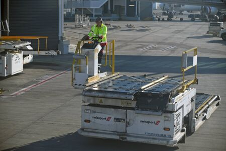BRISBANE, AUSTRALIA, JULY 27, 2019: An unidentified luggage handler at Brisbane International airport steers his luggage handling machine towards the aeroplane, ready to unload its cargo.