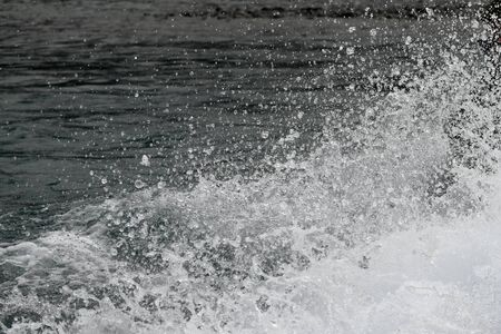 background of a spray of water and water droplets left in the wake of a jet boat