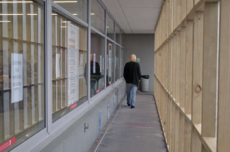 GREYMOUTH, NEW ZEALAND, APRIL 11, 2020: A customer walks through a temporary entrance to create social distancing at a supermarket during the Covid 19 lockdown in New Zealand, April 11,  2020. The red strips on the floor are spaced two metres apart. Editorial