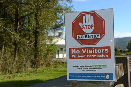 Signage shows that an essential business has restricted access during the Covid 19 lockdown in New Zealand, March 2020 Editorial