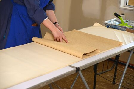 A woman rolls up some glued wallpaper, ready to decorate a bedroom Stock Photo