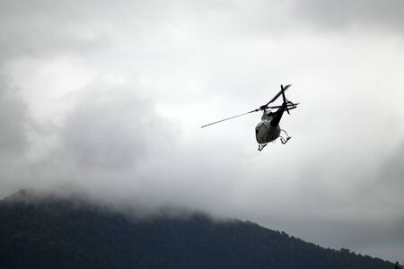 A large helicopter takes off into a cloudy sky Stock Photo