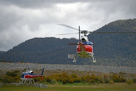 FRANZ JOSEF, NEW ZEALAND, OCTOBER 5, 2019; Tourist helicopters operating at Franz Josef village carry tourists to the world famous glacier in the Southern Alps Stock Photo