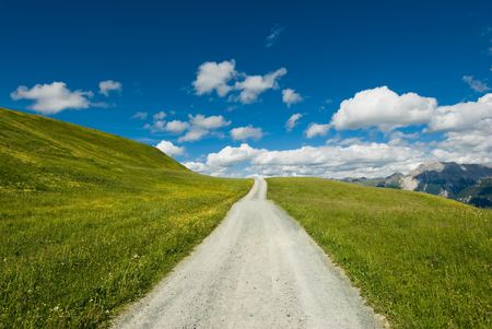 Mountain road on wide open green meadow in swiss alps.