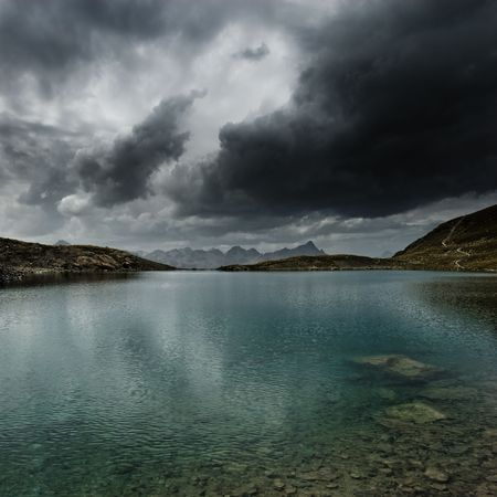 Mountain lake with storm and dark clouds, Engadin, Switzerland photo