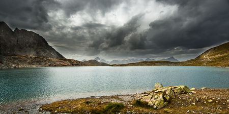 panoramic view of a storm approaching a lake in swiss alps Stock Photo