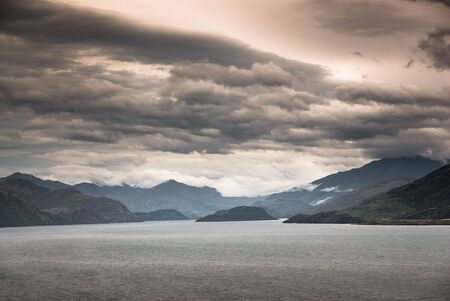 scenic view at lake wanaka at dusk with coulds, south island, new zealand photo