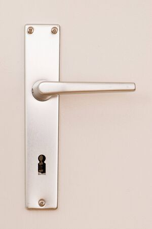frontal view of a clean metal doorhandle on a bright painted door Stock Photo - 4829311