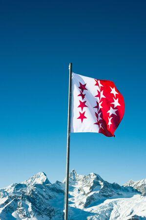 wallis: Flag of canton Wallis, Switzerland with snow mountains in the background, Zermatt, Switzerland