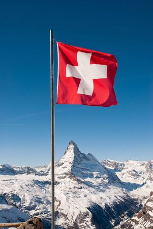 A mountaintop view of the national flag of Switzerland with the Matterhorn in the background Stock Photo