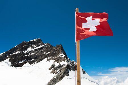 jungfraujoch: National Flag of Switzerland with the Jungfrau mountain peak Stock Photo