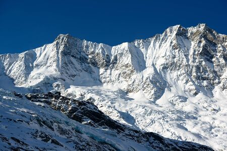 dom: Dom and Taeschorn mountain peaks with Laengflueh in winter. Saas Fee, Switzerland Stock Photo