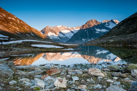 the silence of the world: Mountain panorama from Maerjelensee in early morning with Fusshorn and Dreieckshorn. Part of the Jungfrau-Aletsch UNESCO World Heritage, Wallis, Switzerland.