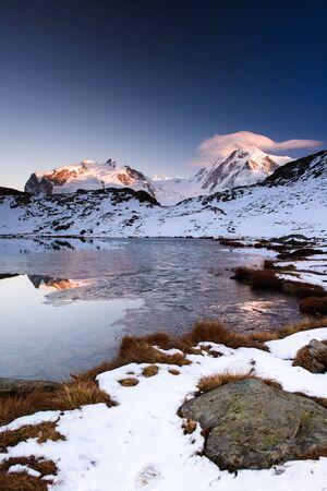 zermatt: Monte Rosa an Lykamm mountain peak at sunset from Riffelsee, Gornergrat, Zermatt, Switzerland