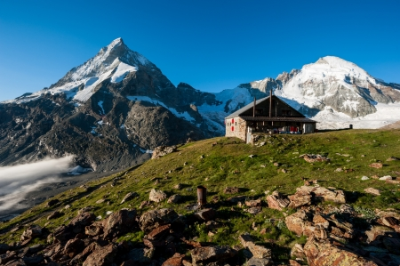 refuge: Panorama with Schoebiel SAC mountain hut with matterhorn and dent dherens mountain peaks, Zermatt, Valais, Switzerland.