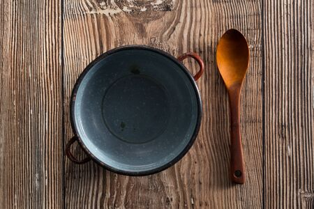 destitution: Spoon with empty cooker on a table