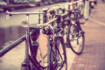 secured: Secured Aged Rusty Bikes in Amsterdam. Netherlands Transportation. Vintage Color Grading.