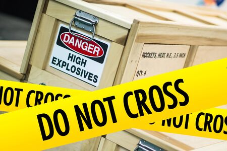 caution tape: High Explosives Danger Concept with Yellow Caution Tape Saying Do Not Cross. Stock Photo