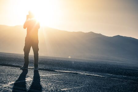 profesar: Hombres con la c�mara tomando fotos The Desert Sun. Foto de archivo